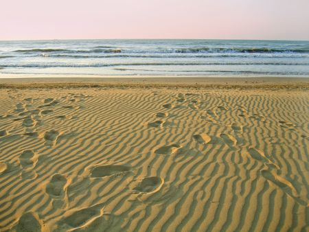 morning empty beach and footprints on sand photo
