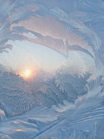 Frosty natural pattern and sun on winter window