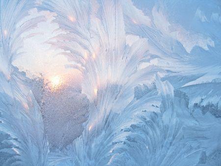 frosty natural pattern and sun on winter window Standard-Bild