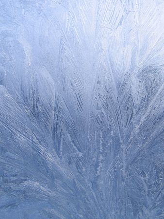 blue frosty natural pattern on winter window photo
