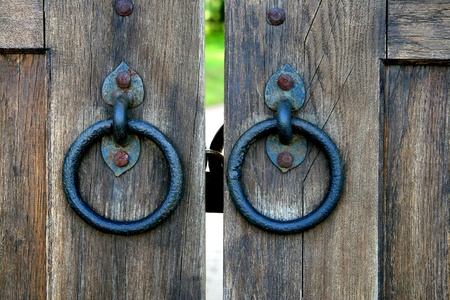 door bolt: ancient wooden gate with two door knocker rings Stock Photo