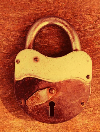 old rusty padlock on wooden background photo