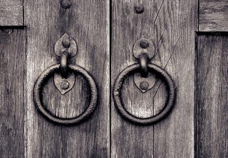 ancient wooden gate with two door knocker rings Standard-Bild
