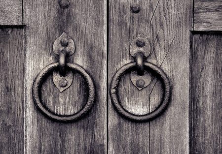ancient wooden gate with two door knocker rings Stock Photo