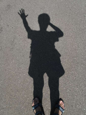 shadow of a man with a raised hand on the gray asphalt                                photo