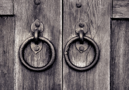 Ancient wooden gate with two door knocker rings photo
