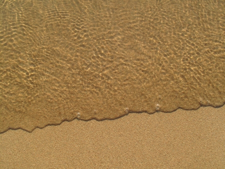 Transparent sea wave on the sand photo