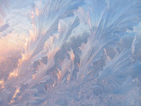 Frosty natural pattern and sunlight on winter glass photo