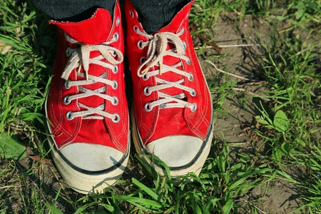 Feet in red sneakers in green grass  photo