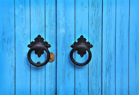 Bright blue wooden door with round handles photo