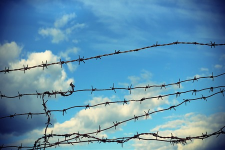 Barbed wire against blue sky with clouds photo