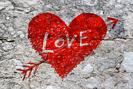 Drawing of abstract heart pierced by an arrow with word Love on grunge stone wall texture photo