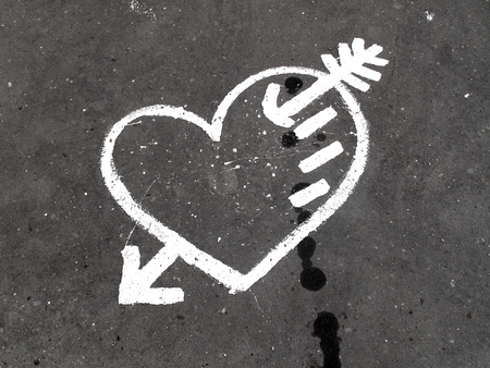 Abstract white heart painted on the dirty pavement                            photo
