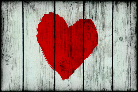 Bright red abstract love symbol on old wooden grunge wall photo