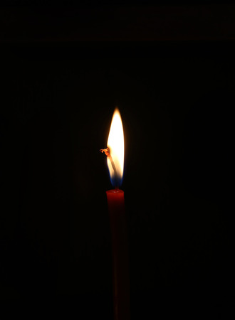 vertica: Closeup of bright burning candle in the dark Stock Photo