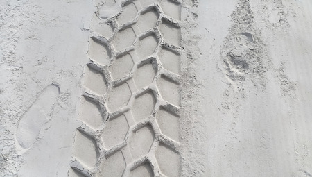 crankle: Wheel track and footprints on the sandy beach Stock Photo