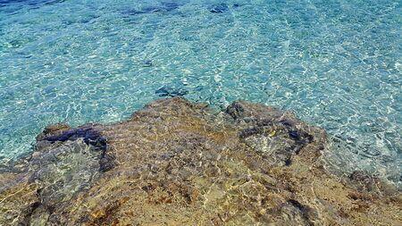 wavelet: Bright sea water and coastal rocks nature background Stock Photo