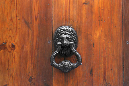 Lion Head Door Knocker on wooden background Stock Photo