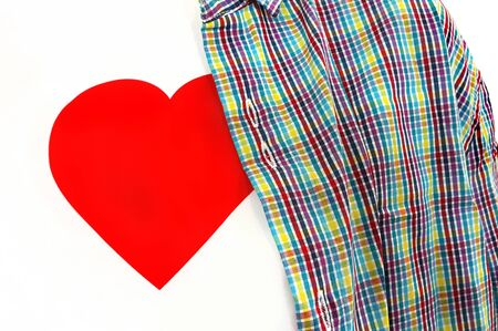Closeup of T-shirt with a red heart on a white background under colorful checkered unbuttoned shirt Stock Photo