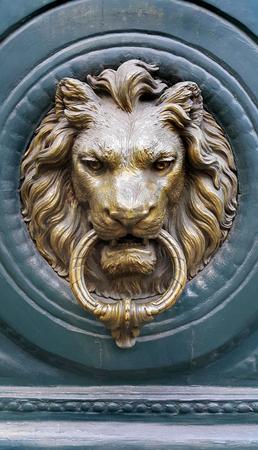 Doorknocker with head of Lion on a green wooden door, Paris, France Редакционное