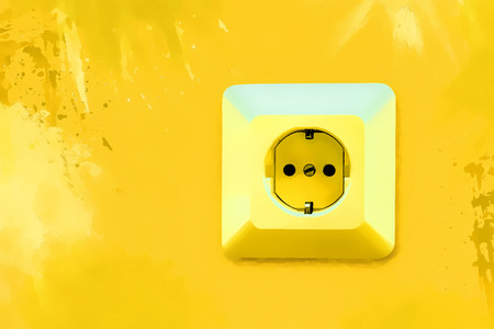 Electric socket on bright yellow wall with blots Stock Photo