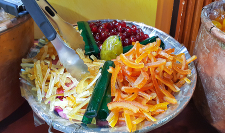 Appetizing candied fruit on a large plate, close-up