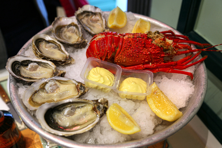 Large dish with fresh seafood, oysters with lobster with lemon and sauce on ice in a restaurant Foto de archivo