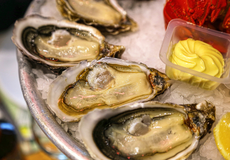 Close-up of dish with fresh seafood, oysters with sauce on ice in a restaurant