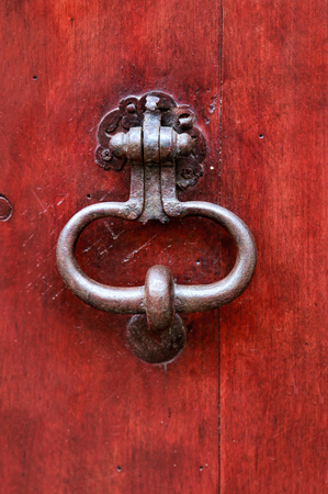 Vintage bright red wooden door with metallic knocker,Troyes, France