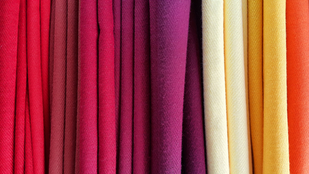 Bright multicolored background of fabrics, close-up texture