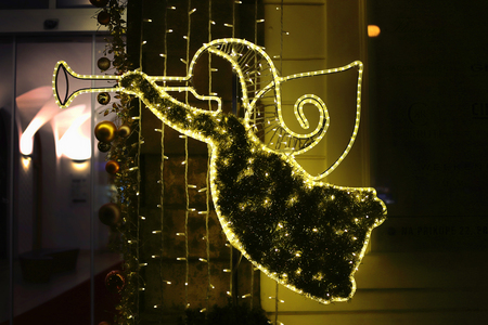 Christmas glowing decoration in the form of abstract angel with trumpet in evening Prague, Czech Republic Stock Photo