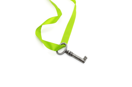 Vintage silver key with green ribbon isolated on white background