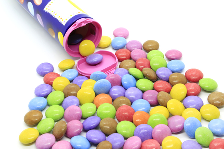Bright multicolored glazed chocolate candies out of the container on a white background 스톡 콘텐츠