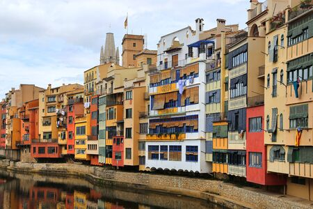 Colorful old houses reflected in water river Onyar, Basilica of Sant Feliu in Girona, Catalonia, Spain