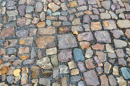 Old pavement of stones of different colors and sizes as a background Stockfoto