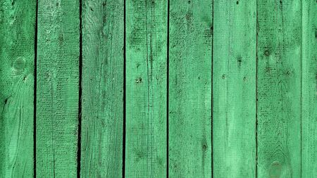 Texture of weathered wooden green painted fence, close-up vintage background
