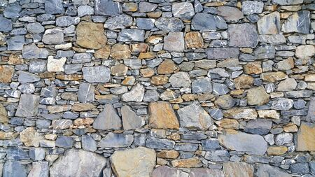 Old wall from stones of various shapes, architectural background