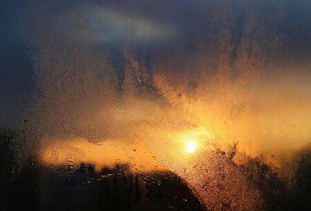 Schmelzendes Eis, Wassertropfen und Sonnenlicht auf einer Fensterscheibe an einem Wintermorgen, natürliche Textur in Nahaufnahme