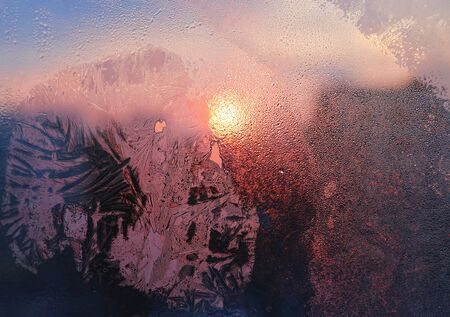 Ice patterns, water drops and sunlight on a window glass on a winter morning, close-up natural texture