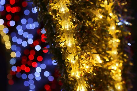 Bright Christmas decoration, colorful lights of bulbs, garlands and shiny tinsel, abstract background out of focus