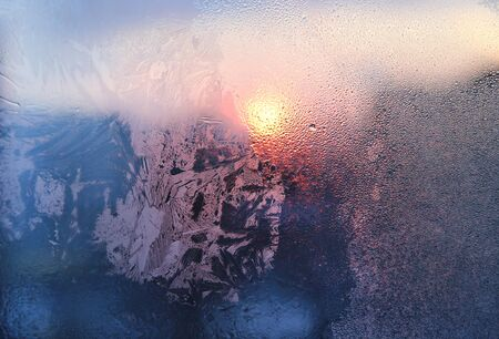 Amazing ice pattern and water drops on a frozen window glass on a sunny winter morning, close-up natural texture
