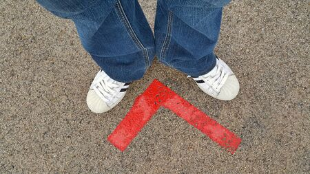 Legs in sneakers and blue jeans standing on the pavement with a bright red arrow Imagens