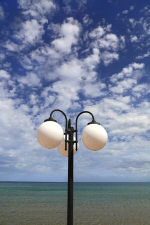 Street lamp against the blue sky with white clouds and sea, Crete, Greece