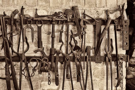 Close-up of vintage work tools hanging on rack at blacksmith shop Archivio Fotografico