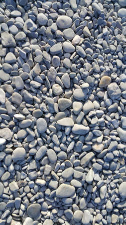 Background from gray sea pebbles, close-up natural texture