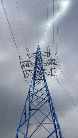 High voltage post or high voltage tower against the cloudy sky in bad weather with bright lightning strike Standard-Bild