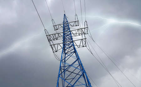 High voltage post or high voltage tower against the cloudy sky in bad weather with lightning strike