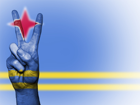 aruba: Hand showing the international symbol for peace, decorated in the national colors of Aruba
