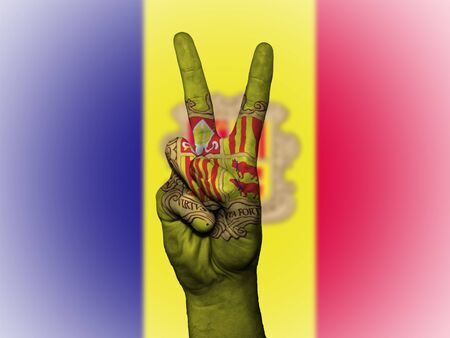 Hand showing the international symbol for peace, decorated in the national colors of Andorra Stock Photo