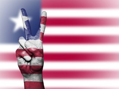 Hand showing the international symbol for peace, decorated in the national colors of Liberia Stock Photo
